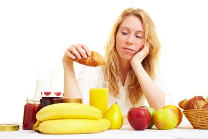 Blonde Frau sitzt mit Croissant am Frühstückstisch