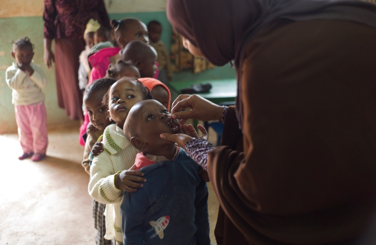 May 7, 2014 - Kwale County, Kenya - Nutritionist Subirah Kassim 25, gives a dose of vitamin A to Suleiman Munyazi, 3, as his baby class peers await their turn, at Jameelah ACK Academy (an Early Childhood Development Center) during Malezi Bora; a week in which maternal and child health care services are provided to community members. (Photo by Ric Francis)