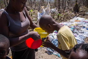 On 12 October 2016 in Jérémie, Haiti, a boy drinks water from a small bucket. A tanker truck in the area provides chlorine-treated spring water to temporary shelters for the displaced. ACTED, a UNICEF implementing NGO-partner, is working in partnership with the national water branch, DINEPA, to ensure the purification of the water delivered. Hurricane Matthew passed over Haiti on Tuesday October 4, 2016, with heavy rains and winds. While the capital Port au Prince was mostly spared from the full strength of the class 4 hurricane, the western area of Grand Anse, however was in the direct path. The cities of Les Cayes and Jeremie received the full force sustaining wind and water damage across wide areas. Coastal towns were severely damaged as were many homes in remote mountainous regions. International relief efforts are underway to provide food water and shelter to the people affected by the storm. An estimated 500,000 children live in the Grande Anse Department and Grand South Department in southern Haiti, the areas worst hit by Hurricane Matthew. UNICEF had prepositioned emergency supplies with national authorities to reach up to 10,000 people. On 8 October, six water trucks arrived in Jeremie and Les Cayes, the respective capital cities within the Departments. Additional water and sanitation supplies, such as water purification tablets, water bladders and plastic sheeting, have been dispatched to the most affected departments in the westernmost tip of Haiti. As of 10 October, UNICEF delivered blankets, buckets, water purifying equipment and cholera diagnostic kits. UNICEF is working to reinforce good hygiene practices, especially in temporary shelters, in order to minimize the outbreak of disease. An investigation is underway to confirm the areas affected by cholera, and to determine the cross-over with hurricane-affected areas.