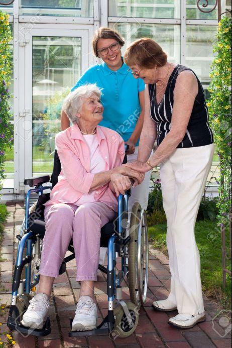 32264427-close-up-paciente-anciano-en-silla-de-ruedas-con-dos-cuidadores-capturados-en-jard-n-con-el-edificio-foto-de-archivo