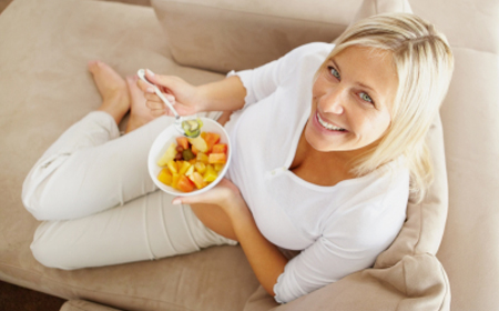 Top view of a middle aged woman relaxing on couch and eating fruit salad