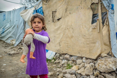 """Recently escaped from militia held territory, Syrian refugee girl, Rahaff, 5, with her doll in an informal tented settlement in Bakaa, Lebanon. Mom – Khadija Daughter – Rahaff, 5 Son – Ahmed, 2 (not in photos) Khadija and her two children escaped from Syria to Lebanon five months ago. They came from a region that was under the control of militants who declared that no one was allowed to leave. Her husband paid a smuggler $250 so that she and the children were smuggled out through back country in a pickup truckload of sheep. """"Food had become so expensive that we couldn't afford it,"""" says Khadija. """"When they [the militant group] took control, they made many rules and changed them frequently to be stricter. It was very dangerous for women. If a woman got caught in public without a man from her family, she would be taken to the mosque. Then they would go to pick up the guys from her family and beat them, throw them in prison, or kill them."""" """"It is much better for us here, even though we have no assistance,"""" she says. Khadija and her children share a tent with her husband's nephew and his family. Her husband stayed behind to take care of other family members."""
